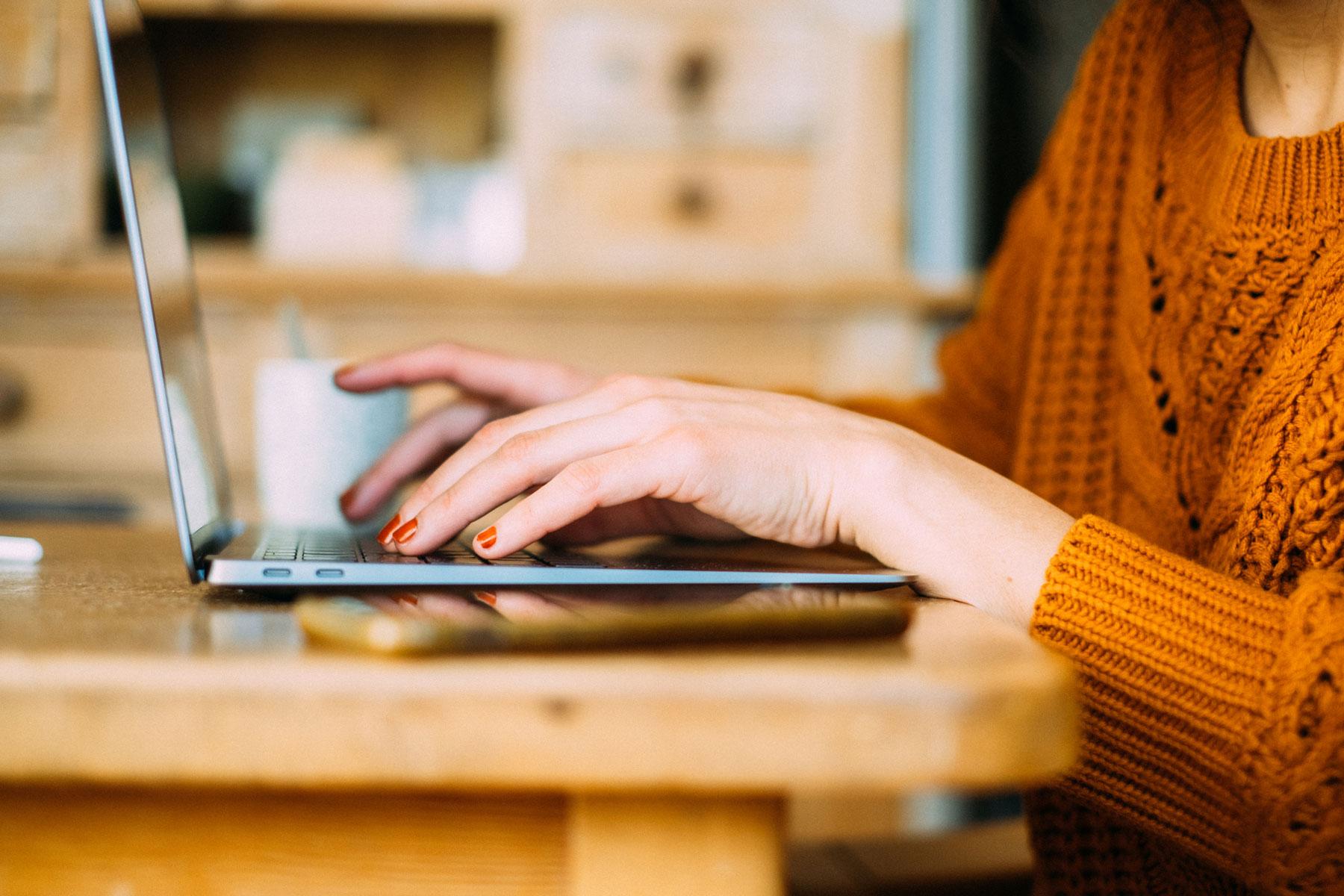 Frau am Laptop mit Strickpulli